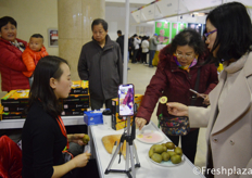 Visitors tasting the Red hearted kiwi fruit from Shanghai Yi Kailong Network Technology Co. Ltd. //访客品尝上海益凯龙网络科技有限公司的红心猕猴桃。