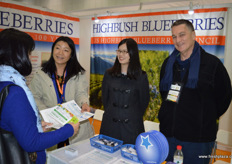"""Julia Zhu, Mandy Chen and Thomas Payna are receiving interested questions from visitors at the stand of the US Highbush Blueberrry Council. // ""朱红芳(Julia Zhu), 陈钰茗(Mandy Chen)和Thomas Payna在美国蓝莓协会展台前接收来自到访者的意向问题。"""