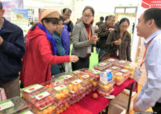 Visitors are eagerly trying some tomatoes at the stand of Volpusi, tomato grower and breeder from Shandong Province in China. // 山东夏之秋果蔬有限公司展位前的访客正在热切地尝试一些番茄,该公司是一家位于中国山东省的番茄种植商和栽培商。