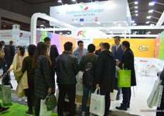People have gathered at the stand of RKG Asia to enquire about and taste the Dori, and Italian kiwifruit variety currently being exported to China // 人们聚集在 爱奇果园亚洲有限公司展台前询问有关Dori的信息并进行品尝,Dori 是目前出口到中国的意大利猕猴桃。