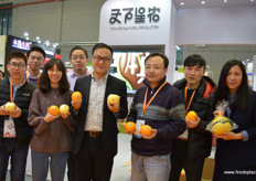 """The Agricultural Revolution from Beijing is bringing new brands on the market. This is the company's orange variety and brand. Chinese domestic brands are becoming more common and developing rapidly. Hu Hai Qin, in the middle in a white shirt, is the company's director and marketing strategist. ""北京的天下星农投资发展有限公司为市场 带来了新品牌。这是该公司的橙子品种和品牌。中国国产品牌正在变 得越来越普遍,发展迅速。中间穿着白色衬衫的,是该公司的总裁和 营销战略家胡海卿"""