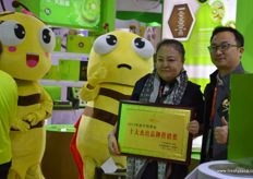 Helen Gong, President of the Shaanxi Betrue Organic Fruit Industry Group is receiving a brand award for the company's BE TRUE organic kiwifruit brand. To the right is Zender, organisator of Hi Fresh // 陕西本真有机果业集 团的总裁宫妤,为其本真品牌接收品牌奖,右边是亚洲果蔬博览会的 组织者朱勇立