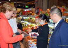 Staff of Olé are trained to give out fruit samples and information. To the left, Cathy Burns, CEO of PMA. // 华 润万家的员工接受提供水果样品和信息的培训。左边是农产品营销协会 的首席执行官Cathy Burns。