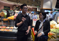 To the left the store manager of the Yonghui Superstores outlet, who is giving a short store introduction. To the right Mabel Zhuang, PMA's representative in China. // 左 边是永辉超市的商店经理,他真正做一个简短的店面介绍。右边是农产 品营销协会在中国的代表Mabel Zhuang。