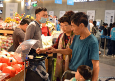 Customers trying out some freshly cut fruits at Hema Fresh. // 客户正在盒马尝试切好的水果。